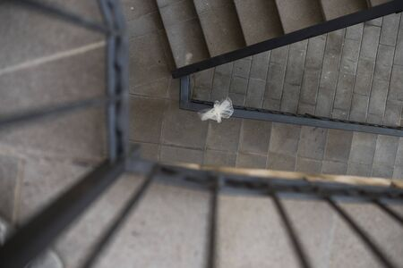 An outdoor staircase in golden section with a white wedding bow tied to it to mean a concept