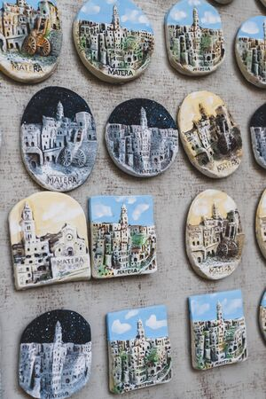 Many colorful magnets on the fridge of the urban landscape of Matera on a door of a souvenir shop Banco de Imagens