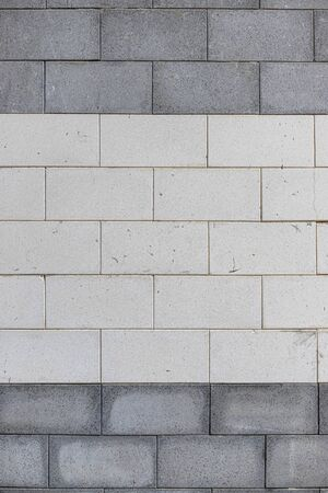 Close up outside view of a gray and white wall made of rectangular stone bricks. Structured surface with parallel lines and geometric shapes. Image of a facade with dark traces