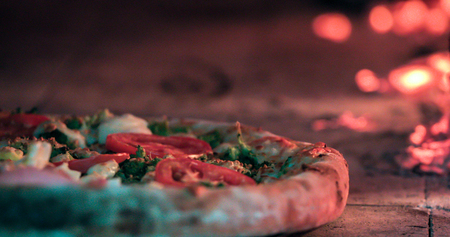 Delicious pizza being roasted in traditional wood oven Imagens