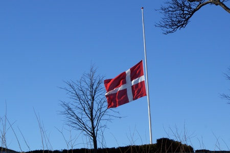mourn: Danish flag swaying on half during burial  Stock Photo