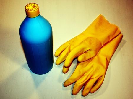 Botella con productos químicos y guantes de goma para la protección