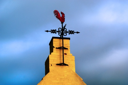 Weather vane on a stormy and cloudy sky photo
