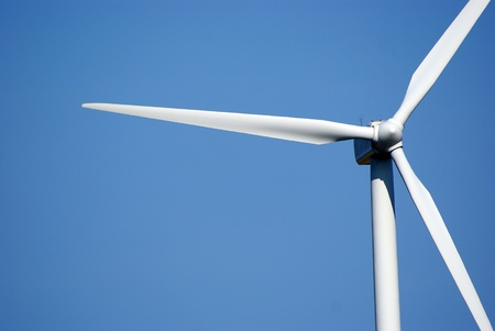 Wind turbine, close against blue sky photo