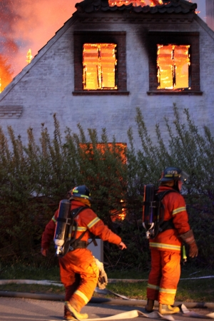 House on fire and two fire fighters Stock Photo