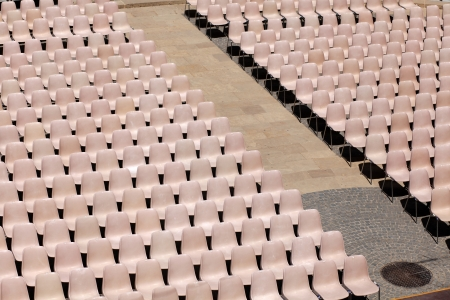 lined up: Many light rosa chairs lined up for concert, speach or other event