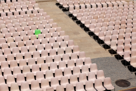 The green V I P chair, many light rosa chairs lined up for concert, speach or other event photo