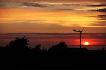enjoyable: Small private windtubine stands in enjoyable sunset