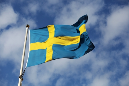 Waving swedish flag against blue sky with small white clouds photo