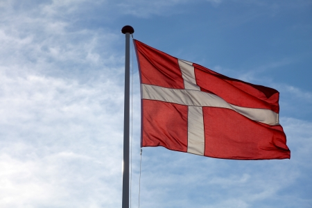 The Danish flag Dannebrog waving against blue sky photo