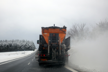 Behind truck spreading salt on icy road.