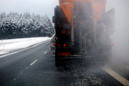 Truck spreading salt on slippery road.