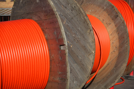 Huge orange cable drums for optic fibre connections. Stock Photo