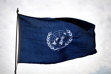 The flag of the United Nation waving in the wind against the sky Editorial