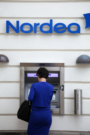Blue dressed woman make a withdravel from Nordea cash point