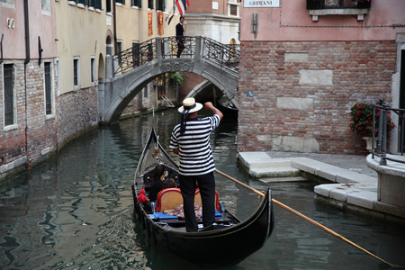 Gondolier on a gondola in the small canals of Venice