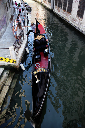 Gondolier with his gondola in the small canals of Venice, getting ready for the next customers Editorial