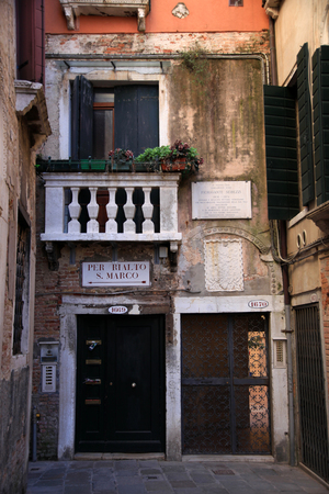 Narrow path between houses and buildings in Venice. With directions to san Marco and Rialto, Italy