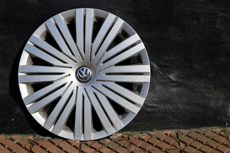 Volkswagen hubcap rolled of a car and put on the sidewalk.