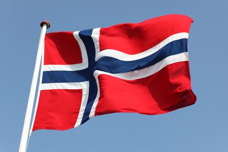 Norways Flag on flagpole against blue sky. Stock Photo