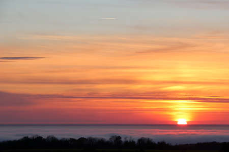 A rare phenomenon over the Baltic Sea where the sea is covered by a thin layer of clouds as seen here from Bornholm towards Sweden at sunset. Stock Photo