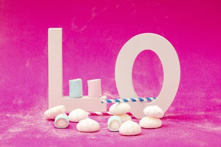 Letters L and O with marshmallows and blue straw on a pink background