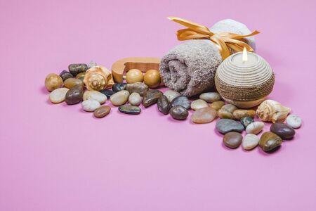 Spa essentials, aroma sticks, stones, towels and a plant on a pink background
