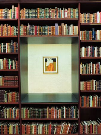 Una libreria in legno con molti libri antichi.