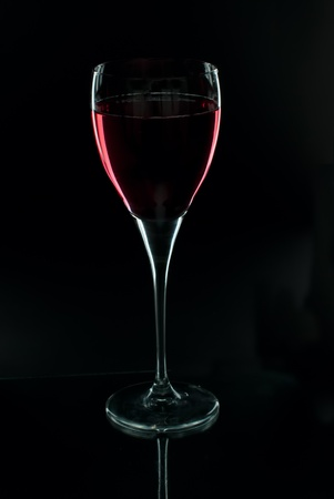 glass of red wine on a black background photo