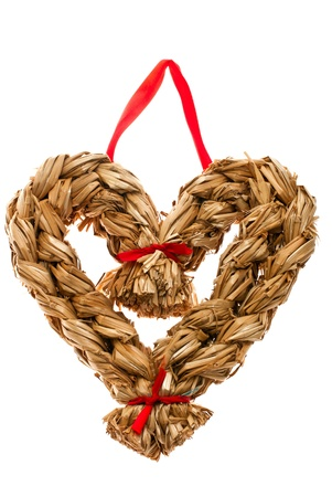 Christmas decoration hand made from straw in shape of heart isolated on white Stock Photo