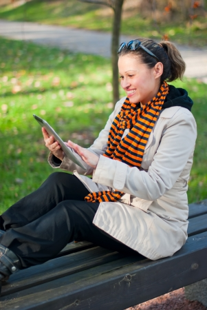 Young woman with pc tablet in the park