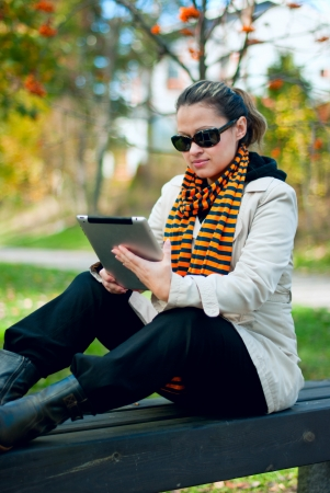 Young girl with tablet PC sitting on a park bench  Focus on the girl, the background is blurred