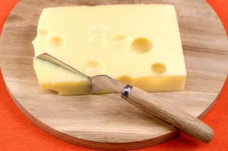 Cheese with a knife on a wooden board