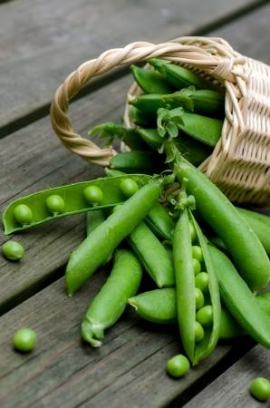 verduras verdes: Guisantes frescos sobre un fondo de tablas viejas Foto de archivo