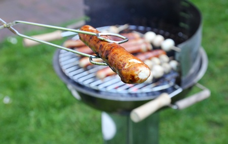 Tongs Holding a Grilled Bratwurst over a hot barbecue grill  photo