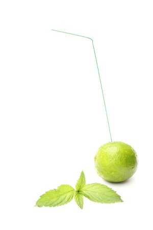 a lime with a drinking straw and fresh mint