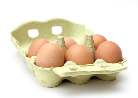 six brown eggs in the package isolated on white background photo