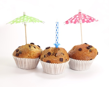 three chocolate muffins with a candle isolated on white background