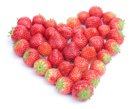 strawberries shaped to form a heart on white background photo