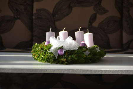 The Christmas wreath with white candles and purple ornament