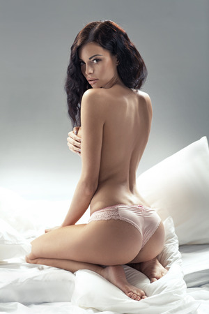 Delicate brunette lady posing in bedroom