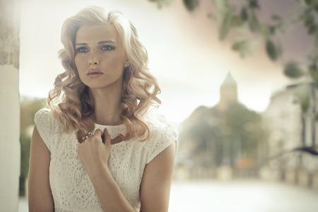 金髪の女性と巻き毛のヘアスタイル屋外ポーズ 写真素材