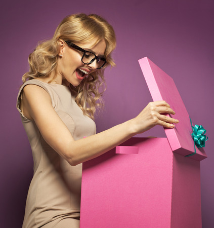 Charming blond woman opening a gift box photo