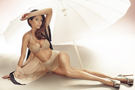 Alluring lady lying under the white umbrella