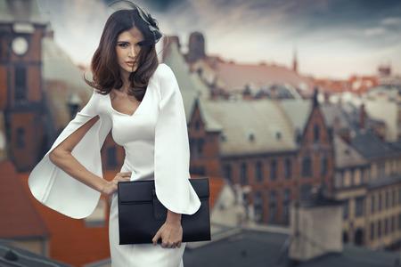 Slimme brunette vrouw met de panorama stad op de achtergrond Stockfoto