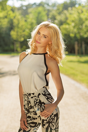 Portrait of the attractive blond girl in the summer park