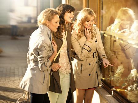 Drie mooie meisjes te kijken naar de etalage Stockfoto