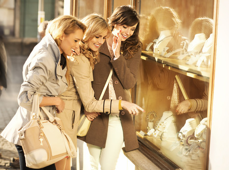 Young cheerful girlfriends looking at the jewellery Imagens