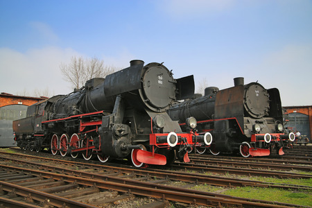 Pair of the huge antique locomotives nex to the garage photo