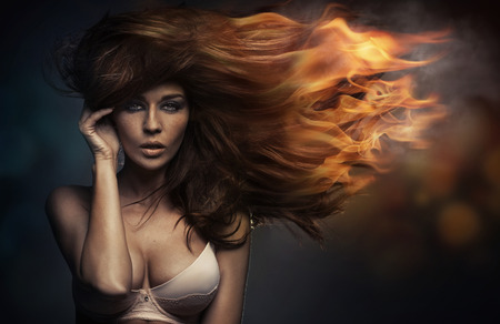 Art portrait of the woman with the flames in hair
